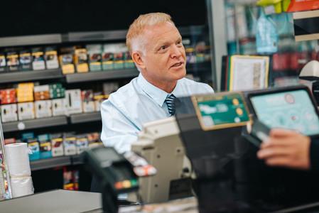 Senior man working at supermarket checkout counter