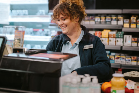 Happy female cashier working at a supermarket