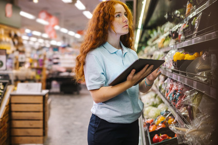 Grocery store employee taking inventory