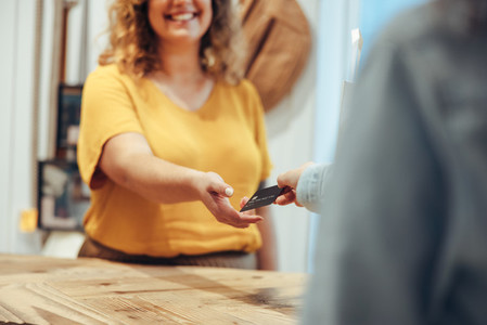 Customer paying by credit card to the saleswoman