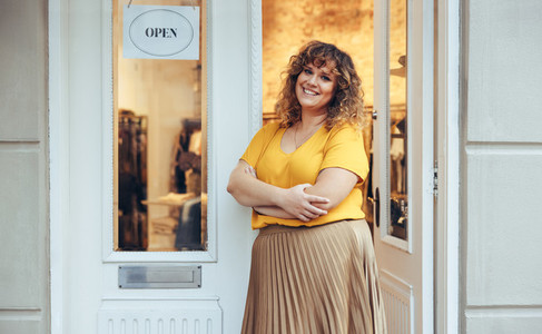 Woman standing at entrance door of her clothing store