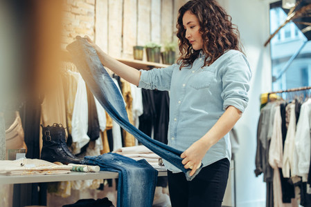 Woman checking quality of jeans in clothing store