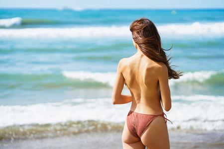 Rear view of topless woman in swimwear enjoying the beach