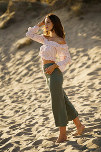 Young beautiful woman standing on the sand of the beach