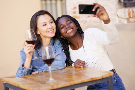 Two women making a selfie with a smartphone while having a glass of wine