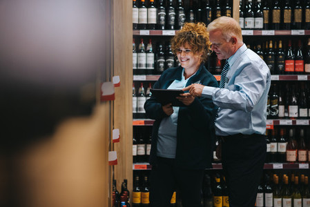 Wine shop employees taking inventory