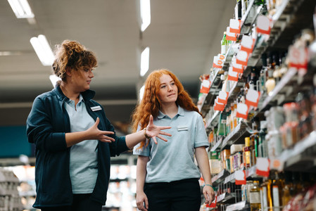 Supermarket manager giving training to a trainee employee