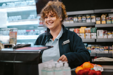 Happy cashier at supermarket checkout