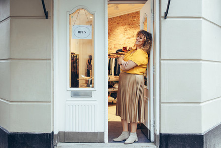 Businesswoman standing at her boutique doorway
