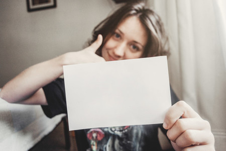 girl smiles while holding a paper with her hands