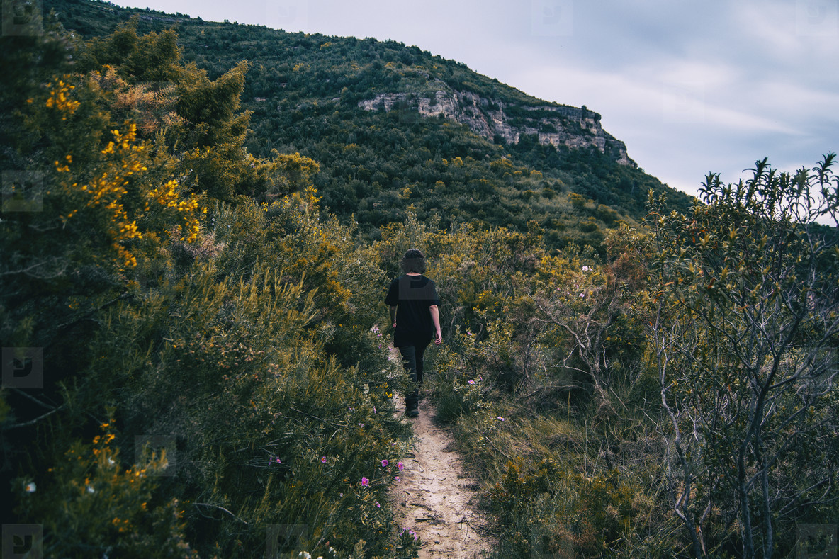 A girl hiker behind her back walking on a mountain path
