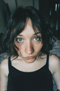 Portrait of a beautiful girl with big blue eyes looking at camera with surprised expression