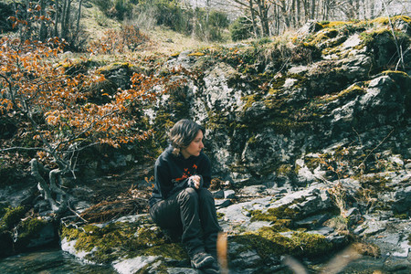 Portrait of a young girl sitting on a mossy rock next to a river