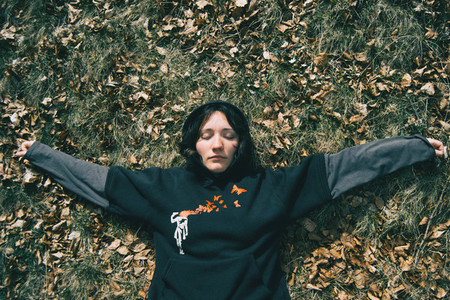 A girl with closed eyes lying down resting in nature