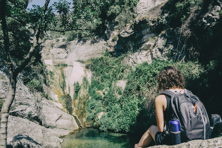 girl sitting on a rock looking at a landscape of a small waterfall