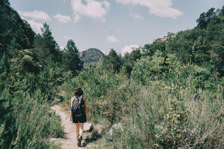 Girl walking along a small path in the mountain of Prades  Tarragona  Spain