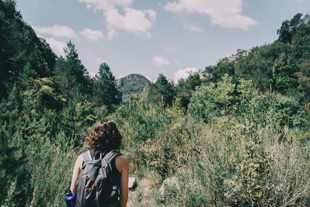 Girl walking along a small path in the mountain of Prades Tarragona Spain
