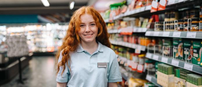 Happy saleswoman in modern supermarket