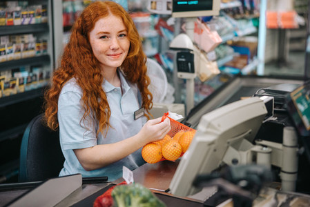 Cashier on checkout in supermarket