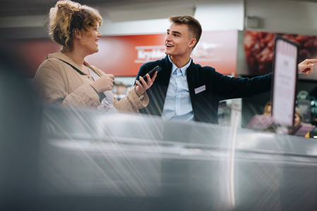 Employee helping shopper at the supermarket