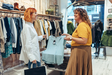 Fashion store owner assisting customer