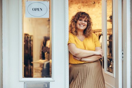 Successful fashion store owner standing at entrance door