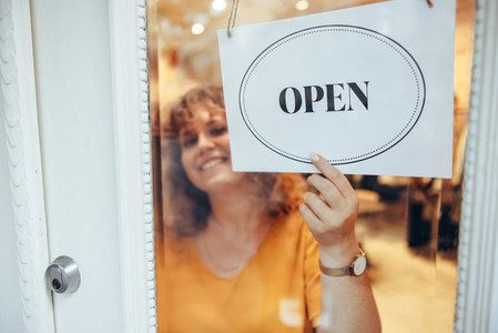 Fashion store owner hanging open sign in front door