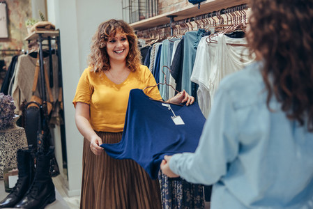 Saleswoman assisting client to find a perfect outfit