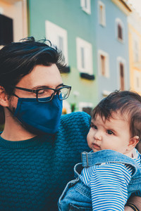 Young father wearing a face mask while hug his baby
