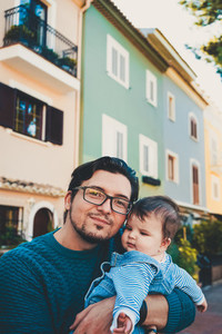 Adorable portrait of a young father hugging his baby