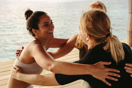 Fitness women enjoying yoga session by the sea
