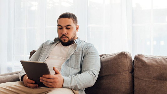 Young man in casual clothes sitting on sofa at home