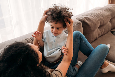 Curly little boy and his mother spending time together at home