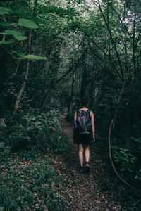 girl walking along a small path that goes into the forest