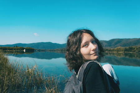 girl sitting on the edge of Banyoles lake with the landscape reflected in the water