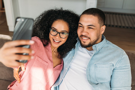 Positive loving couple resting on couch at home and taking selfie on smartphone