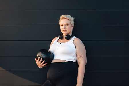 Young woman with a medicine ball at a black wall