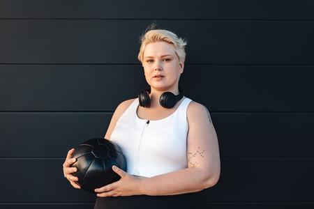 Curvy caucasian woman wearing sports clothes holding a medicine ball