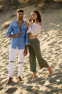 Young couple standing on the sand of the beach