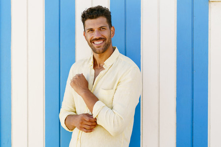 Young man  fashion model  posing in front of a beach booth