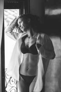 Middle aged woman In lingerie and shirt posing near the window