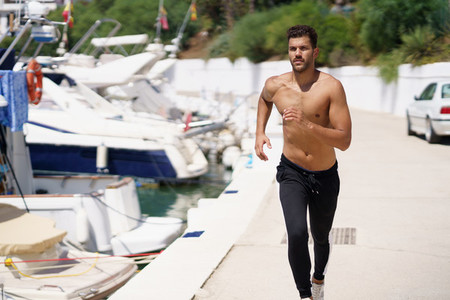 Young man with an athletic body running shirtless through a harbour