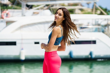 Fitness model in red sportswear outfit posing on waterfront harbour