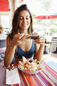 Young woman photographing her salad with a smartphone while sitting in a restaurant