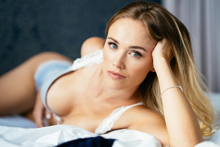 Caucasian girl with amazing blue eyes laying on the bed wearing lingerie