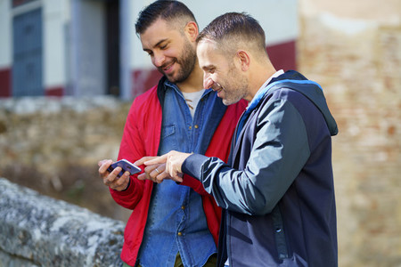 Gay couple looking at their smartphone outdoors