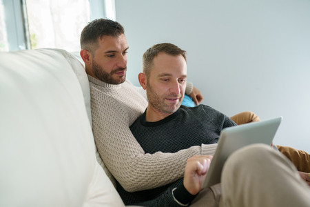Gay couple consulting their travel plans together with a digital tablet