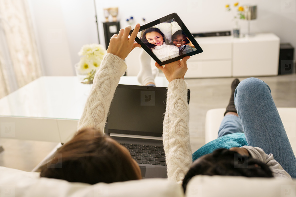 Two female friends making a selfie with a digital tablet sitting on the couch at home
