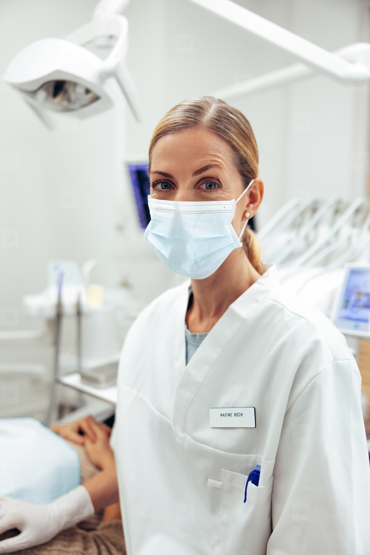 Dentist with face mask in her office