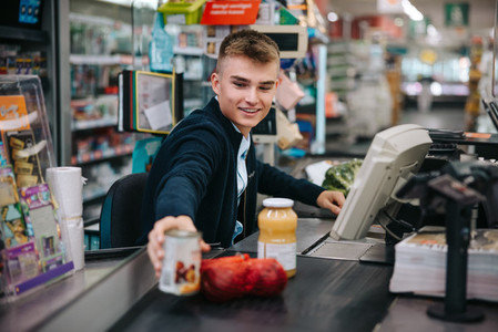 Man serving customers at supermarket checkout